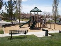 Playground equipment surrounded by benches and trees.